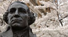 bust of george washington in front of cherry blossoms