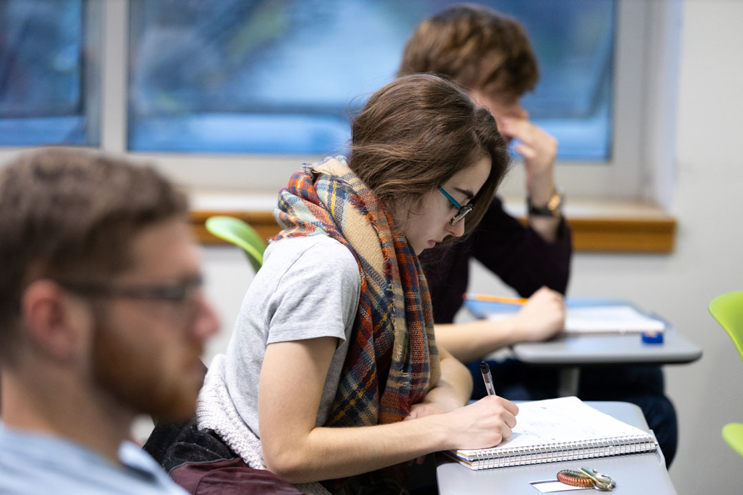 A student writing on her notebook in an economic class