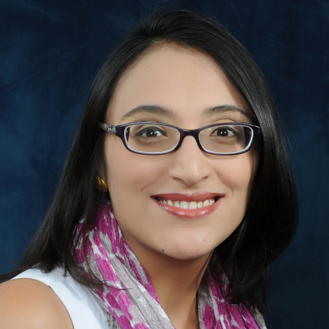 Phd Student, Andrea Lopez-Luzuriaga, wearing a white shirt with a purple and grey scarf in front of a dark blue background