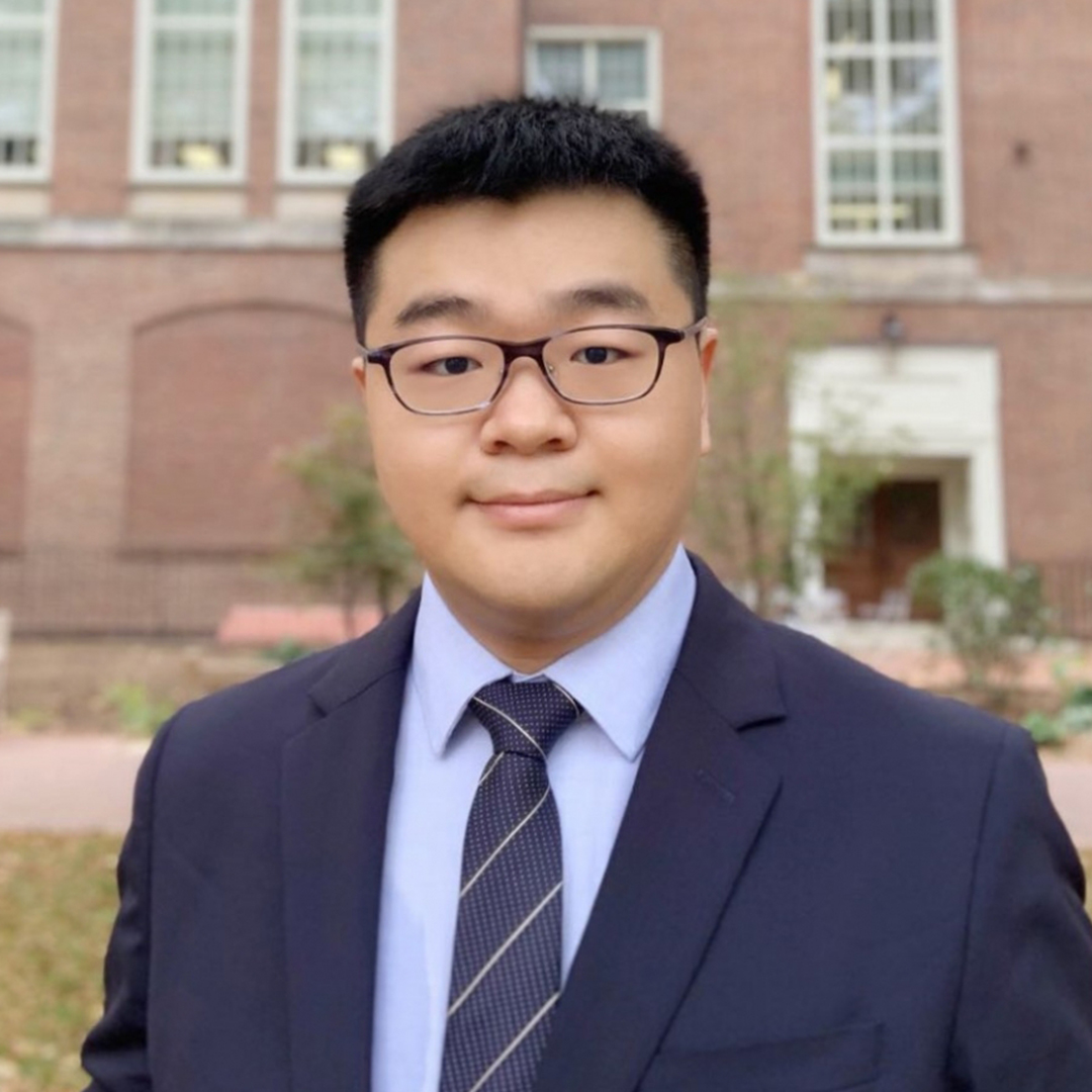 PhD Student, Shiyi Wang, wearing a blue suit and eye glasses in front of a brick building