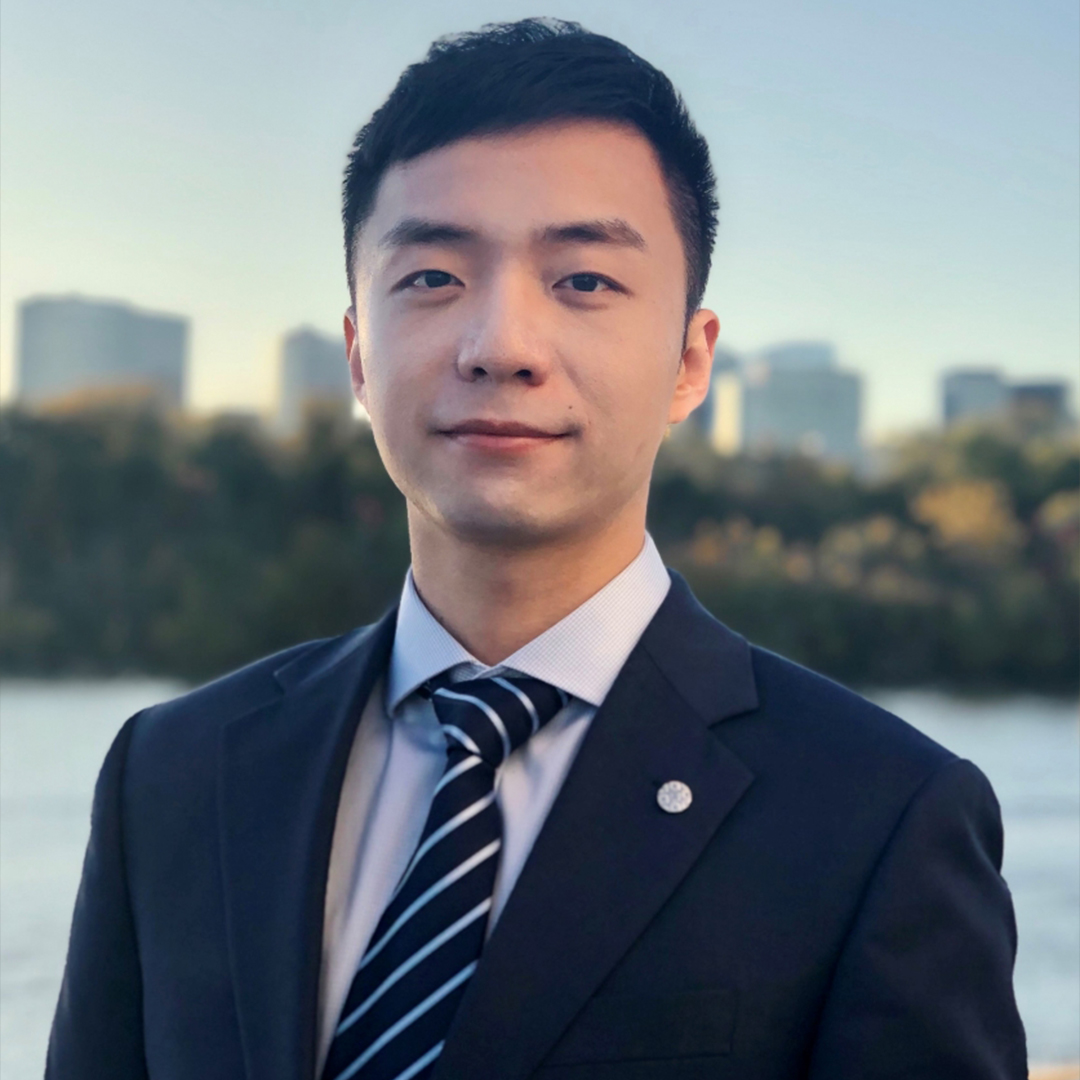 PhD student, Yuxuan Huang, wearing a dark blue suit in front of a city skyline